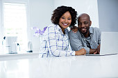 Portrait of happy couple using laptop at home