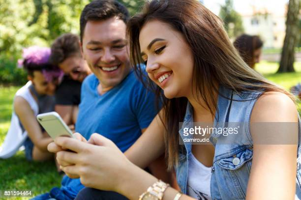 Happy couple using smart phone in the park and smiling