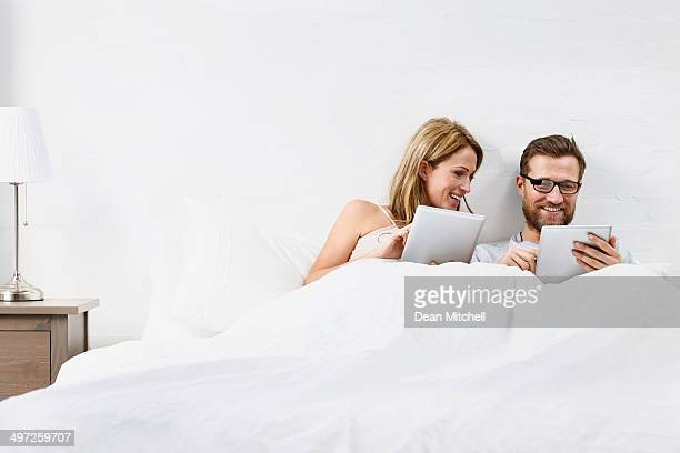 Happy couple using tablet computers on bed