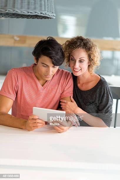 Glückliches Paar mit tablet in der Küche
