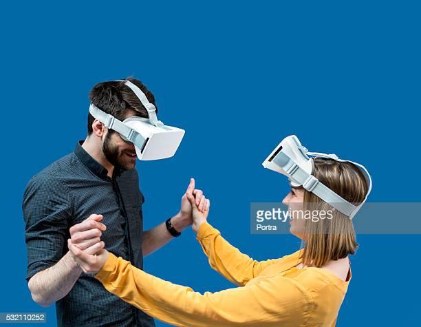 Feliz pareja usando gafas de realidad virtual en pantalla azul