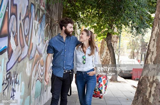 happy couple walking down city street