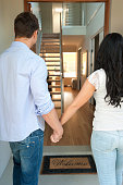 Happy couple walking into their new house