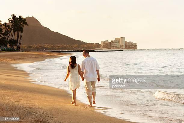 幸せなカップル歩行ワイキキビーチの日の出