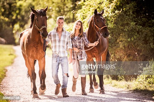 Happy couple walking with horses in nature.