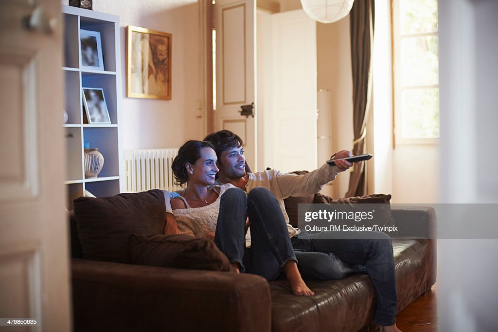 Happy couple watching television on sofa : Stock Photo