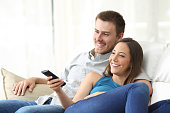 Happy couple watching tv at home sitting in a comfortable couch in the livingroom at home