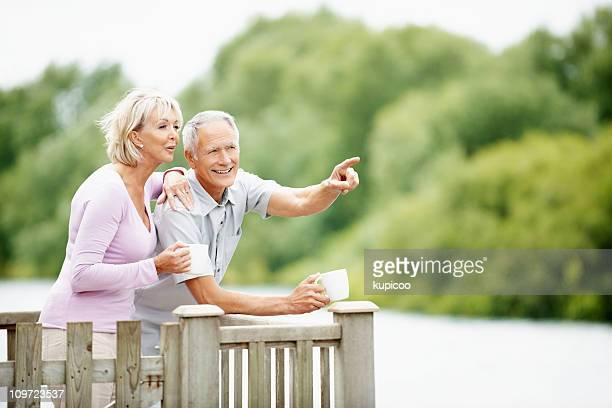 Casal feliz com um homem apontando para algo interessante