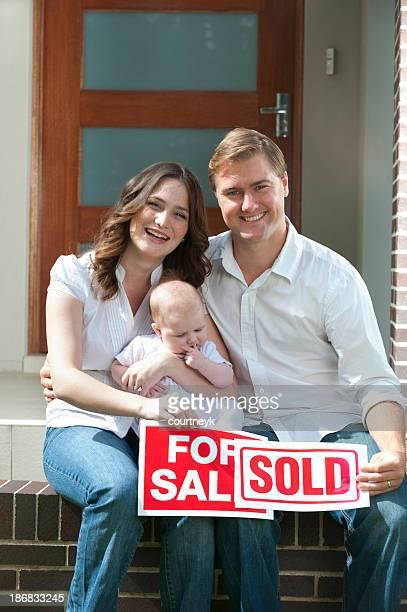 Casal feliz com bebê exploração para sinais de venda e vendidos