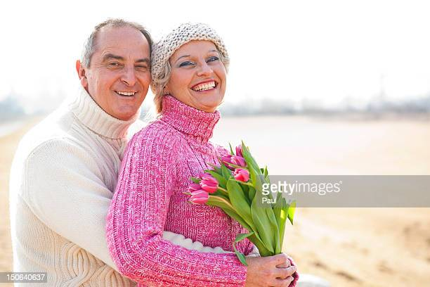 Happy couple with bunch of tulips outdoors