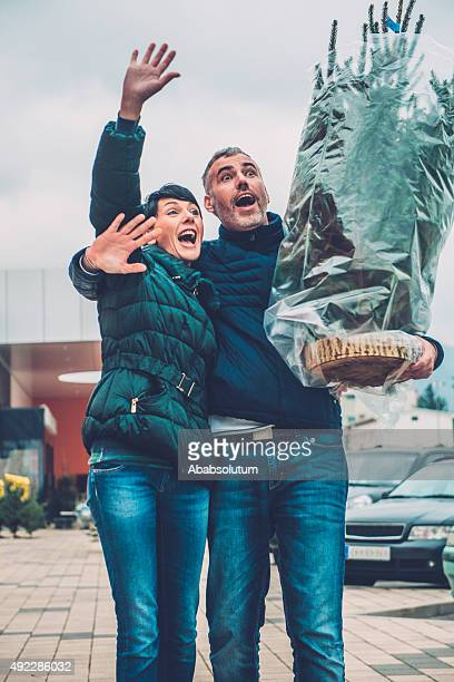 Happy Couple with Christmas Tree Greeting Friends, Europe
