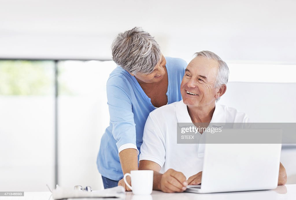 Happy couple with laptop at home
