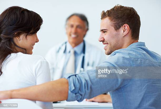 Happy couple with mature doctor