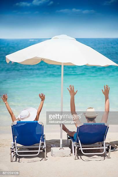 Couple heureux avec mains surélevées en paradis Tropical