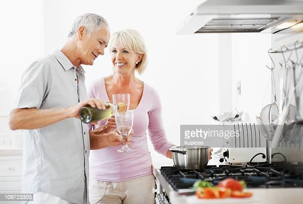 Happy couple with senior man pouring champagne in his glass