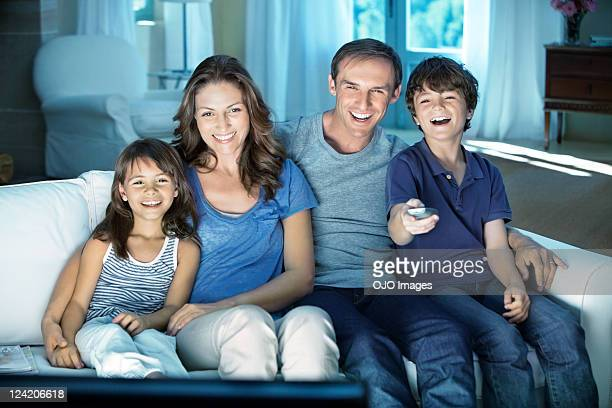 Happy couple with two children enjoying television at home
