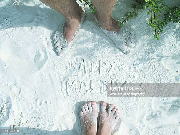 Happy couple's feet on white sand in Maldives