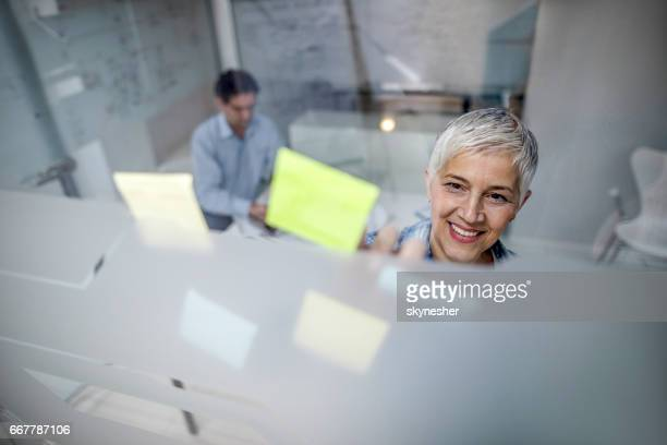 Happy creative woman applying adhesive notes to the glass in the office.