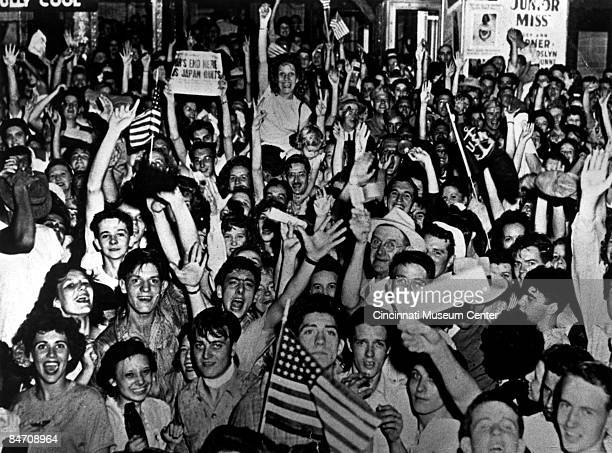 A happy crowd waves flags and copies of the newspaper showing off the headlines proclaiming Japan's surrender Cincinnati Ohio 1945