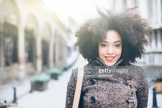 Bouclés heureuse jeune femme devant un bâtiment ancien