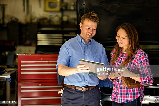 Happy customer discusses repairs with auto mechanic. Digital tablet.