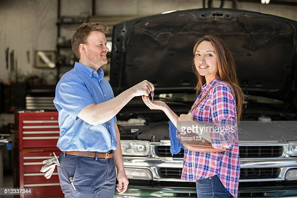 Happy customer gets keys. Satisfied with auto mechanic's great service.