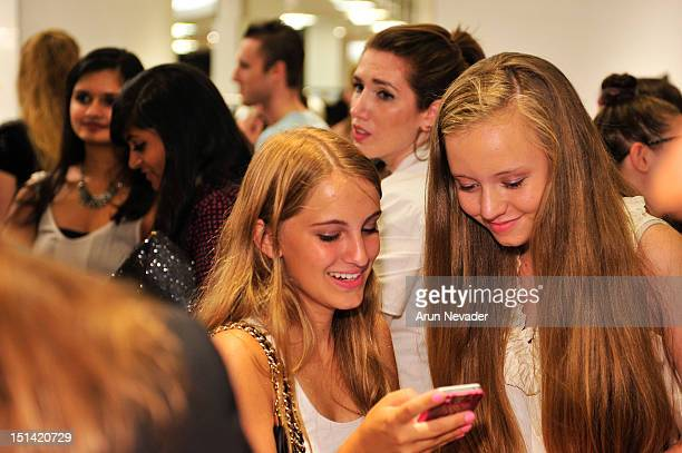 Happy customers play at the Instagram booth during Fashion's Night Out at Saks Fifth Avenue on September 6 2012 in New York City