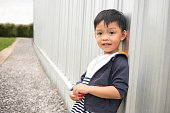 Happy cute boy leaning modern wall of building and perspective way background