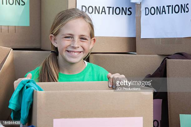 Happy cute girl holding boxes full of donations