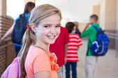 Happy cute little girl elementary student outside school