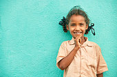 Happy cute poor Indian little girl portrait on wall background.