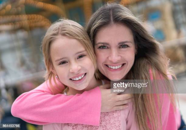 Happy daughter and mother having fun at a carnival