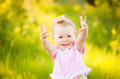 Happy daughter dressed in pink clothes playing at nature. Sunshine spring or summer day