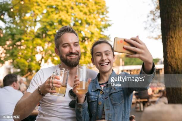 Glückliche Tochter nehmen Selfie bei Getränk im Biergarten