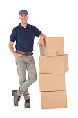 Happy delivery man leaning on pile of cardboard boxes on white background