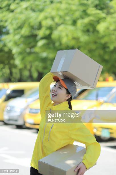 Happy delivery woman holding cardboard boxes
