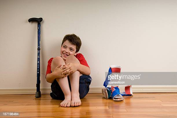 Happy disabled boy sitting on floor with crutches and shoes