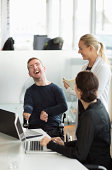 Happy disabled businessman discussing with female colleagues in office