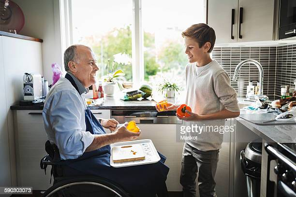 Happy disabled father in wheelchair preparing food with son in kitchen