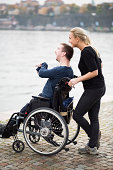 Happy disabled man with caretaker enjoying view by lake
