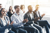 Happy diverse audience applauding at business seminar, in office