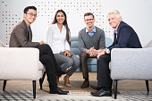 Smiling diverse business partners looking at camera, meeting and sitting in armchairs and sofa in lounge