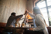 Happy multiracial friends giving high five having fun together in coffee shop, diverse colleagues joining hands celebrating successful project, spending time and chilling out in cafe. Teamwork concept