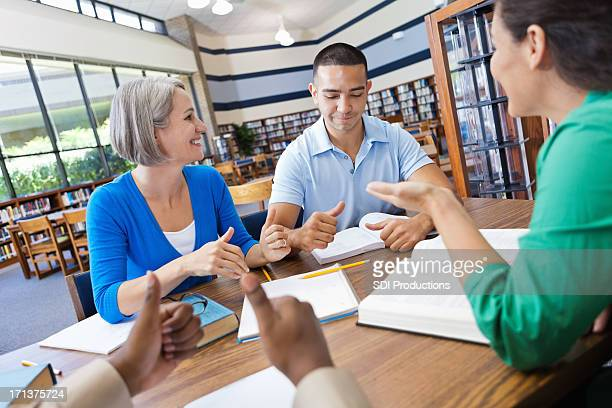 Happy diverse group of friends discussing a book in library
