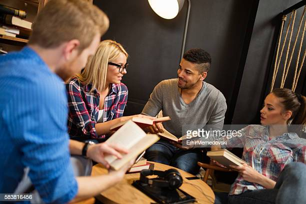 Happy diverse group of friends discussing a book in library.