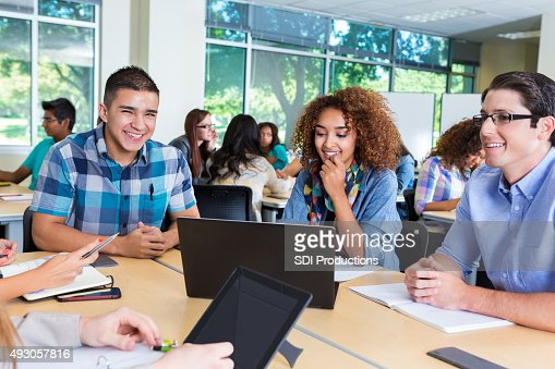 Happy diverse group of high school or college students studying