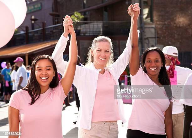 Heureux groupe diversifié des femmes en rose pour célébrer la victoire