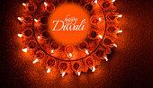 Happy Diwali greeting card design using Beautiful Clay diya lamps lit on diwali night Celebration.  Indian Hindu Light Festival called Diwali, a festival of light
