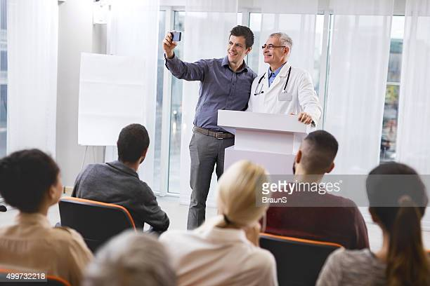 Happy doctor and businessman taking a selfie on education event.