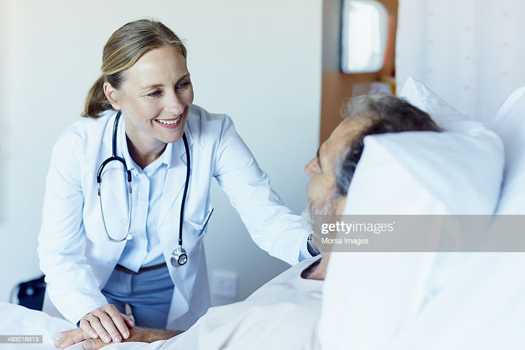 Happy doctor consoling patient in hospital ward